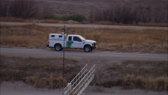 LOW AERIAL U.S. Border Patrol truck on road at US-Mexican border, view of Juarez in distance, El Paso, Texas, USA