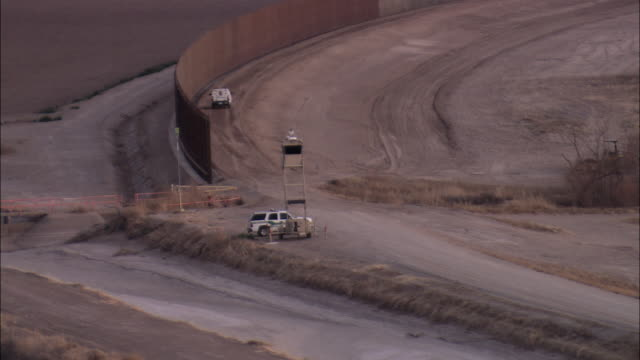 LOW AERIAL U.S. Border Patrol trucks driving on road at US-Mexican border wall, El Paso, Texas, USA