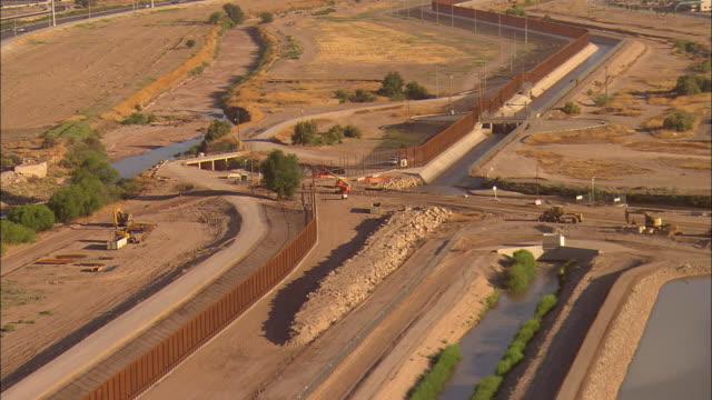 AERIAL US Border Patrol trucks gathered at construction area on 'wall' at US/Mexican border, El Paso, Texas, USA