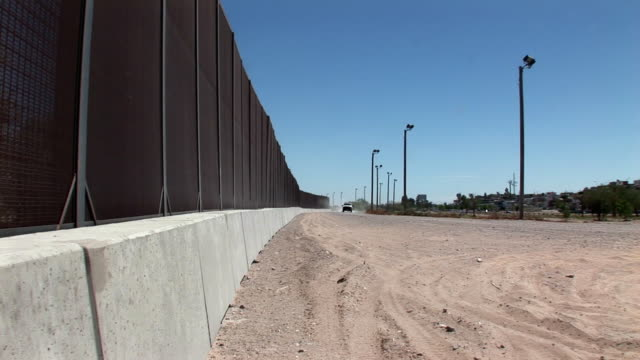 TS PAN ZO Border Patrol vehicle driving next to new high security border barrier, El Paso, Texas, USA
