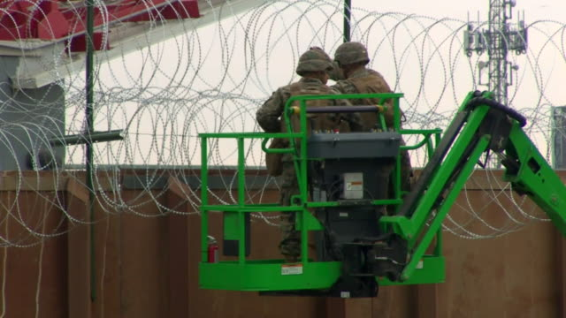 border security on cranes reinforcing barbed wire atop the usa-mexico border fence - 国境の壁点の映像素材/bロール