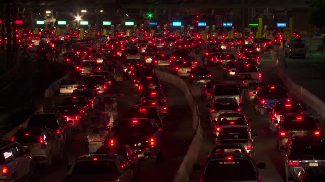 vídeos de stock e filmes b-roll de ws border traffic in tijuana crossing into us at night - cabina de portagem