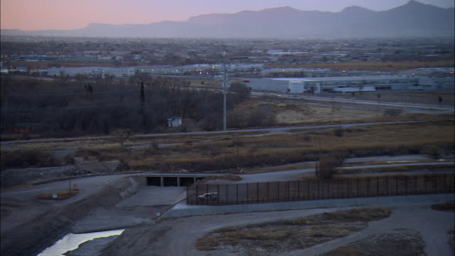 LOW AERIAL 'Border wall' along US-Mexican border at El Paso at sunset, Texas, USA