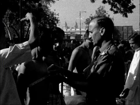 army recuits and protesters in new delhi india new delhi indian men enlist to join army 'recruiting' sign army officer measuring young indian man's... - 1962 stock-videos und b-roll-filmmaterial