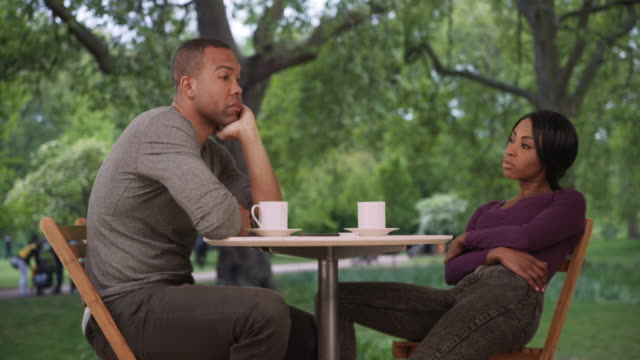 bored black couple drinking coffee sit quietly together at outdoor table - sulking stock videos & royalty-free footage