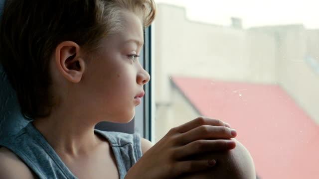 vídeos y material grabado en eventos de stock de chico aburrido en la ventana en su hogar - 10 11 años