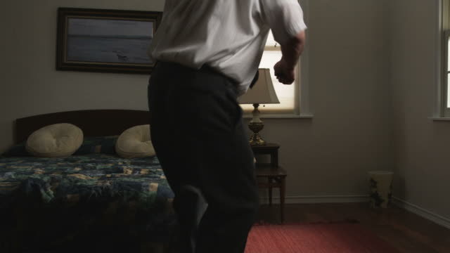 bored businessman passing the time in a hotel room dancing