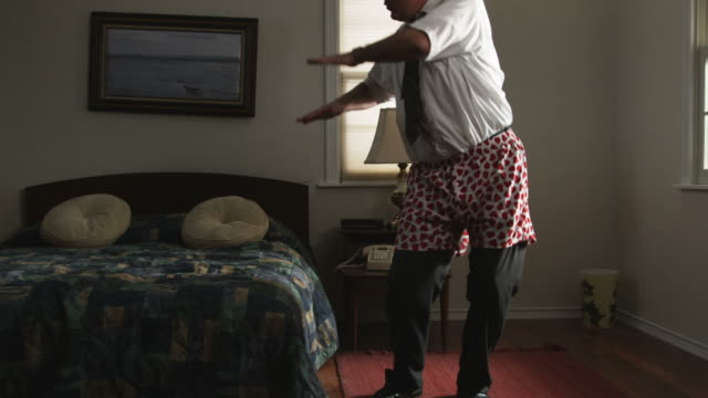 vidéos et rushes de bored businessman passing the time in a hotel room dancing - underwear