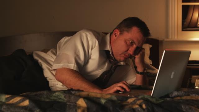 vídeos y material grabado en eventos de stock de bored businessman passing the time in a hotel room on a laptop - acostado