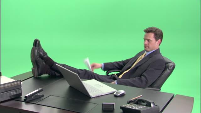 ms, bored businessman throwing paper plane at desk in studio - kostym bildbanksvideor och videomaterial från bakom kulisserna