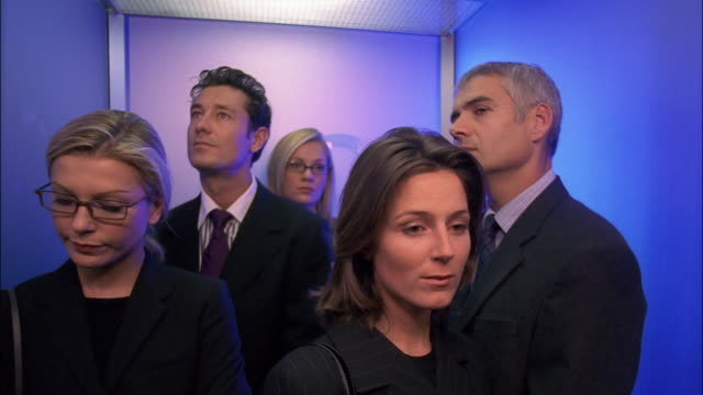 vidéos et rushes de bored businessmen and businesswomen ride in an elevator and then exit when it comes to a stop. - ascenseur