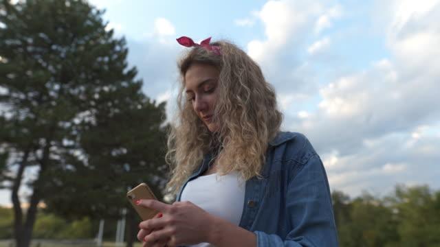 stockvideo's en b-roll-footage met vervelen meisje kijken naar haar telefoon buitenshuis - natuurlijk haar