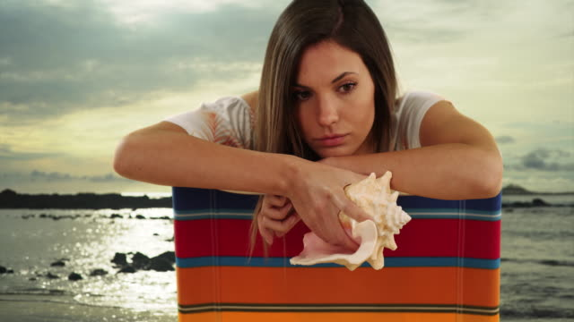bored looking young woman holding conch shell on beach chair by the ocean - seashell stock videos & royalty-free footage