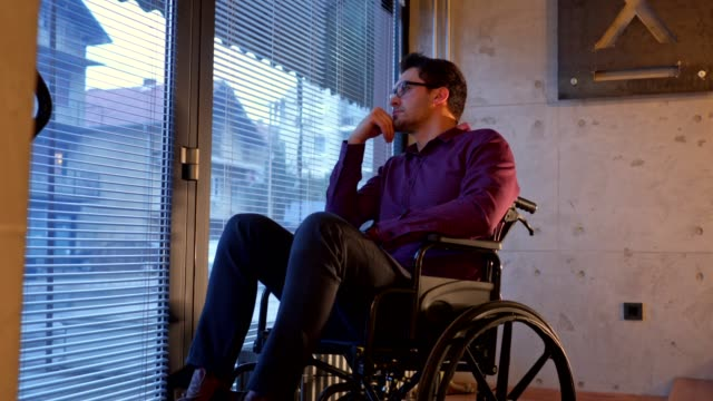 bored man in a wheelchair looking through window - disability stock videos & royalty-free footage