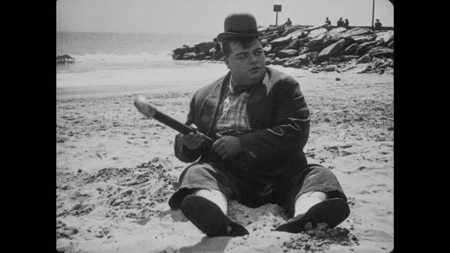 1917 a bored man (fatty arbuckle) sits on beach, flinging sand at irritated reading wife (agnes neilson) before rolling away to get hat - fatty arbuckle stock videos and b-roll footage