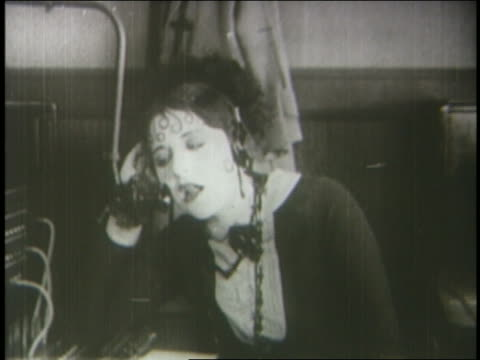 b/w 1924 bored telephone operator chewing gum + talking into receiver - gomma da masticare video stock e b–roll