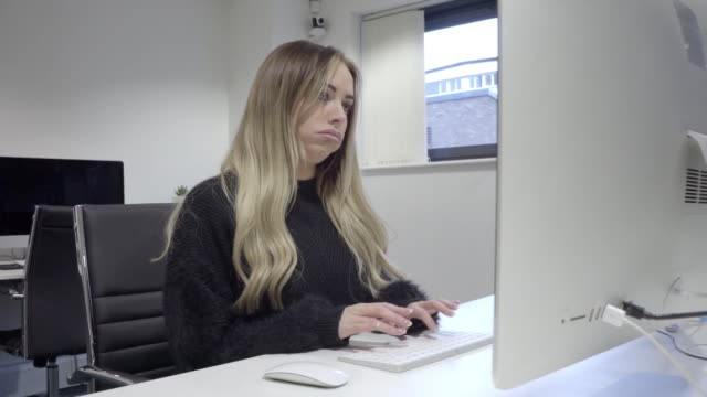 vidéos et rushes de bored tired blonde woman works on computer in office alone - furieux