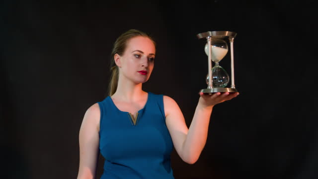 Bored woman holding hourglass