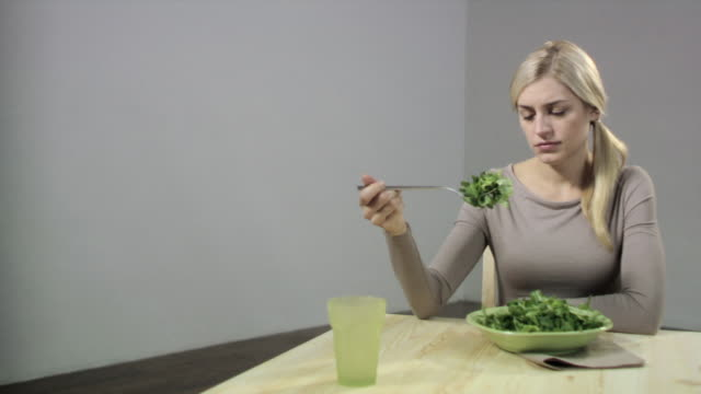 vídeos de stock, filmes e b-roll de bored woman with bowl of salad - dieting