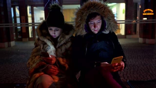 uttråkad ung par som sitter utomhus på en buss stationen väntar - trådbuss bildbanksvideor och videomaterial från bakom kulisserna