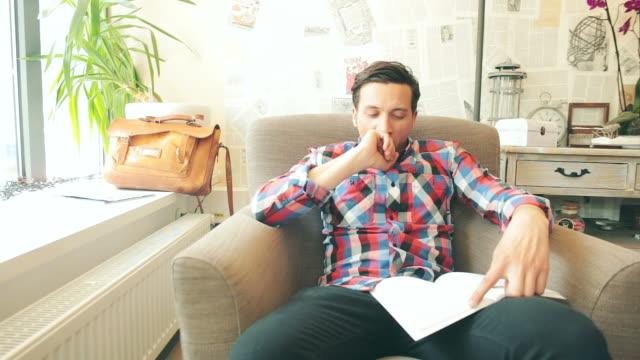 annoiato giovane uomo leggendo un libro. - letteratura video stock e b–roll