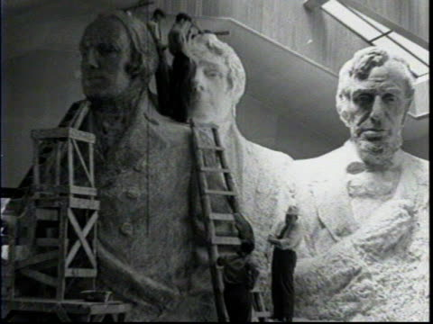 borglum and a reporter standing next to a model of mount rushmore while it's being worked on / gutzon borglum describes the height of mount rushmore... - hügelkette stock-videos und b-roll-filmmaterial
