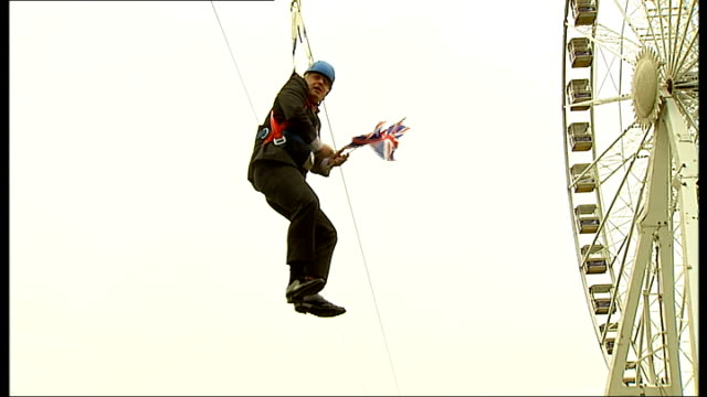 boris johnson gets stuck on zip wire; england: london: victoria park: ext boris johnson along zip-wire waving two union jack flags johnson dangling... - hanging stock videos & royalty-free footage