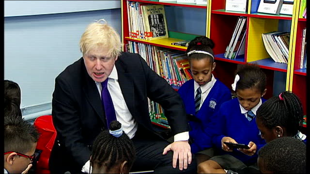 boris johnson helps launch reading festival england london battersea photography*** various shots boris johnson sat in classroom reading 'wind in the... - reading and leeds festivals stock videos & royalty-free footage