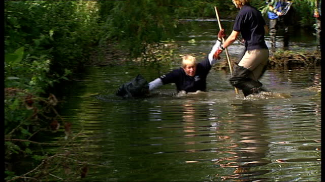 boris johnson helps launch reading festival t04060910 / tx ext boris johnson falls over in river as helping volunteers clear debris from river... - reading and leeds festivals stock videos & royalty-free footage
