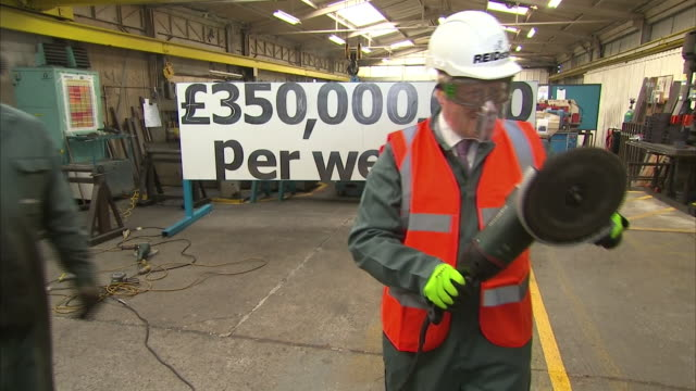 vidéos et rushes de boris johnson holding and using an angle grinder on a visit to a workshop during the vote leave campaign - maire