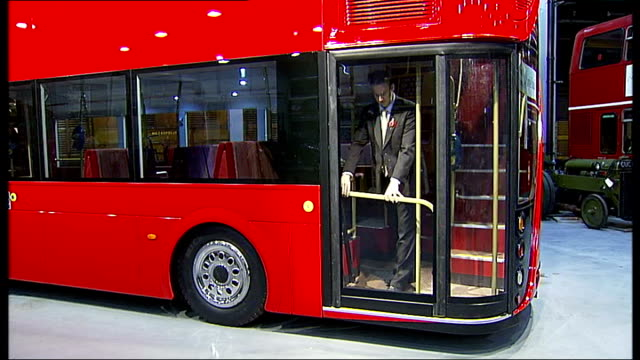 Boris Johnson interview SOT Man closing perspex doors fitted on platform of model of new routemaster bus Front end of routemaster bus Reporter to...