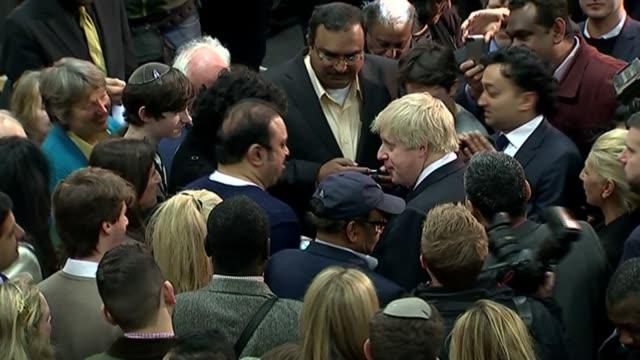vidéos et rushes de boris johnson launches conservative london election campaign int back view boris johnson surrounded by press at launch event zoom in johnson posing... - entourer