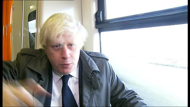 Boris Johnson opens new 'orbital' route on London overground service ENGLAND London EXT Various shots Boris Johnson wearing wooly hat and orange foam...