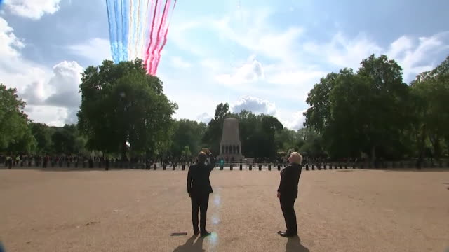 boris johnson pm and president emmanuel macron watch red arrows and patrouille de france flypast as he visits london on 80th anniversary of general... - british military stock-videos und b-roll-filmmaterial