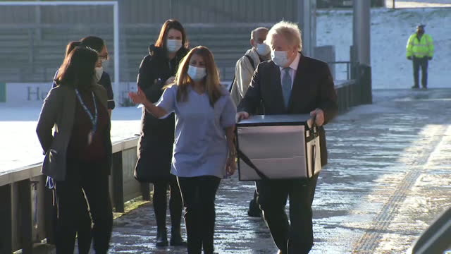 boris johnson pm carrying box of oxford astrazeneca vaccine into boot of car at the hive vaccination centrem barnet fc's grounds in london - box container stock videos & royalty-free footage