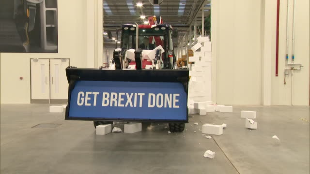 """boris johnson pm drives jcb, emblazoned with """"get brexit done"""" through styrofoam wall with word gridlock written on it, staffordshire - construction machinery stock videos & royalty-free footage"""