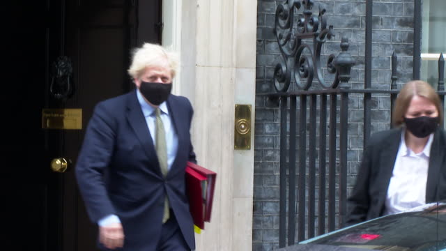 boris johnson pm, leaving 10 downing street to go to prime minister's questions, on the week the three tier coronavirus alert system was announced - domande al primo ministro video stock e b–roll