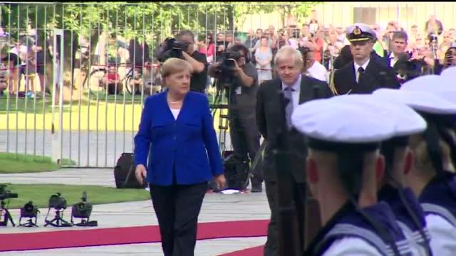 "boris johnson pm walks past guard of honor with angela merkel during meeting at the german chancellery berlin - ""bbc news"" stock-videos und b-roll-filmmaterial"
