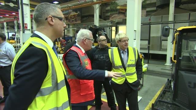 vídeos de stock e filmes b-roll de boris johnson visits jcb factory; england: staffordshire: rocester: int boris johnson mp chatting to workers as looking around jcb factory - tries... - inglaterra