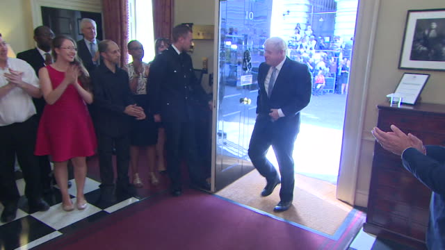 boris johnson walks inside 10 downing street for the first time as prime minister and is greeted by applause by his staff - political party stock videos & royalty-free footage