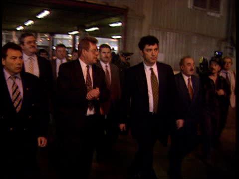 boris nemtsov leads anticorruption drive russia int nemtsov walking thru factory with entourage ext manyon i/c sot ts limousine and escort fast along... - limousine stock-videos und b-roll-filmmaterial