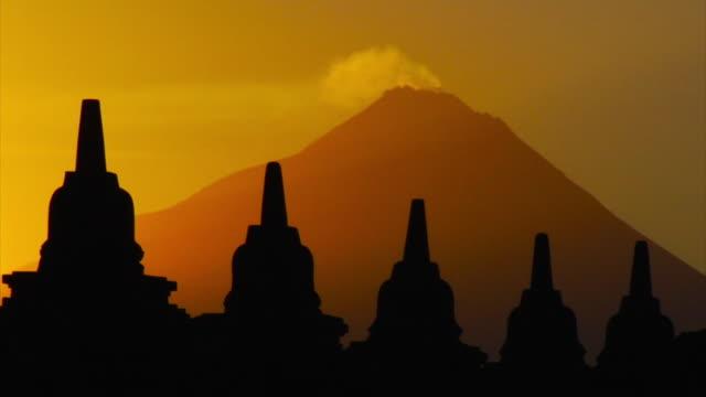 borobudur mahayana buddhist temple with volcano - spirituality stock videos & royalty-free footage
