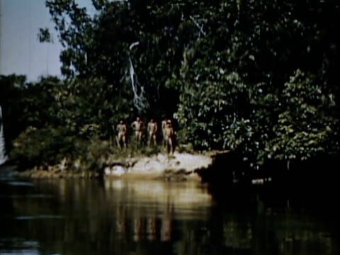 stockvideo's en b-roll-footage met 1954 montage bororo people posing, working and hunting in village / brazil / audio - latijns amerikaanse cultuur
