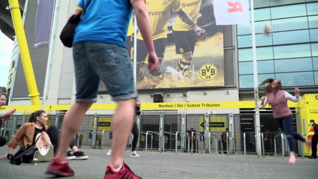 "borussia dortmund fans playing keepy-uppy outside the club's westfalenstadion during the coronavirus crisis - ""bbc news"" stock-videos und b-roll-filmmaterial"