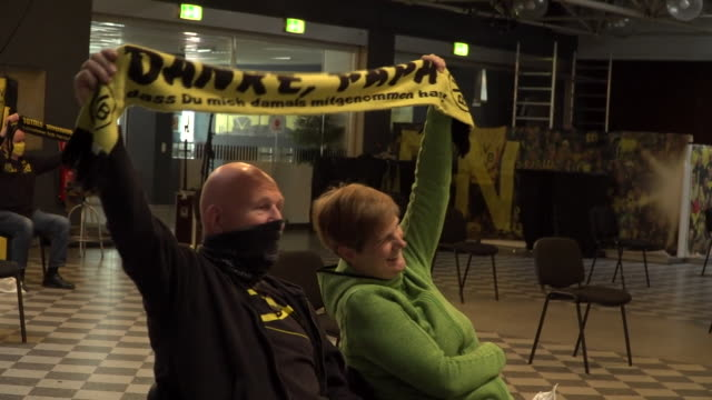 """borussia dortmund fans watching their team play on a big screen whilst maintaining social distancing - """"bbc news"""" stock-videos und b-roll-filmmaterial"""