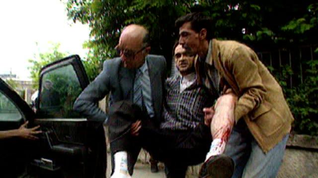 bosnian serb wartime general ratko mladic arrested rtv people along street as hurry when gun fire is heard sot man with bullet hole near shin bone is... - sarajevo stock-videos und b-roll-filmmaterial
