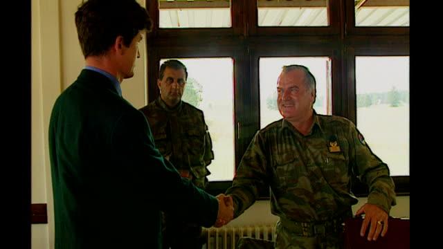 bosnian serb wartime general ratko mladic arrested; tx 5.9.1995 bosnia-herzegovina: int mladic putting papers into case reporter shaking hands with... - ratko mladic stock videos & royalty-free footage