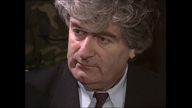 detention camps: radovan karadzic interview; bosnia and herzegovina: bosnian serbs hq: int penny marshall and others seated around table with radovan... - ラドヴァン カラジッチ点の映像素材/bロール