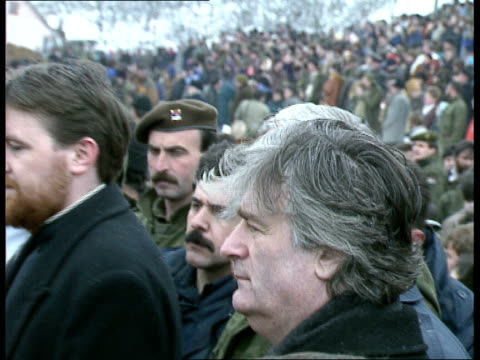 mass grave uncovered in kamenica: funerals / radovan karadzic; radovan karadzic holding candle as stands amongst serbian soldiers and orthodox... - ラドヴァン カラジッチ点の映像素材/bロール