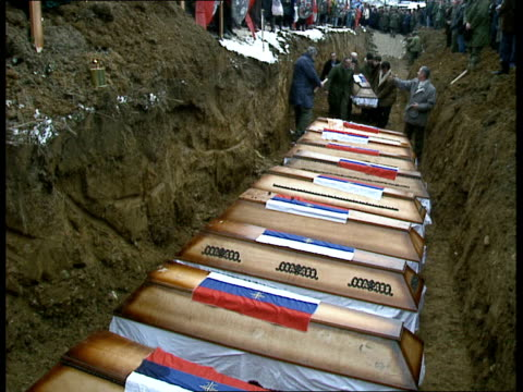 mass grave uncovered in kamenica: funerals / radovan karadzic; serbian troops standing by graveside with wooden crosses and wreaths / various shots... - bosnian war stock videos & royalty-free footage